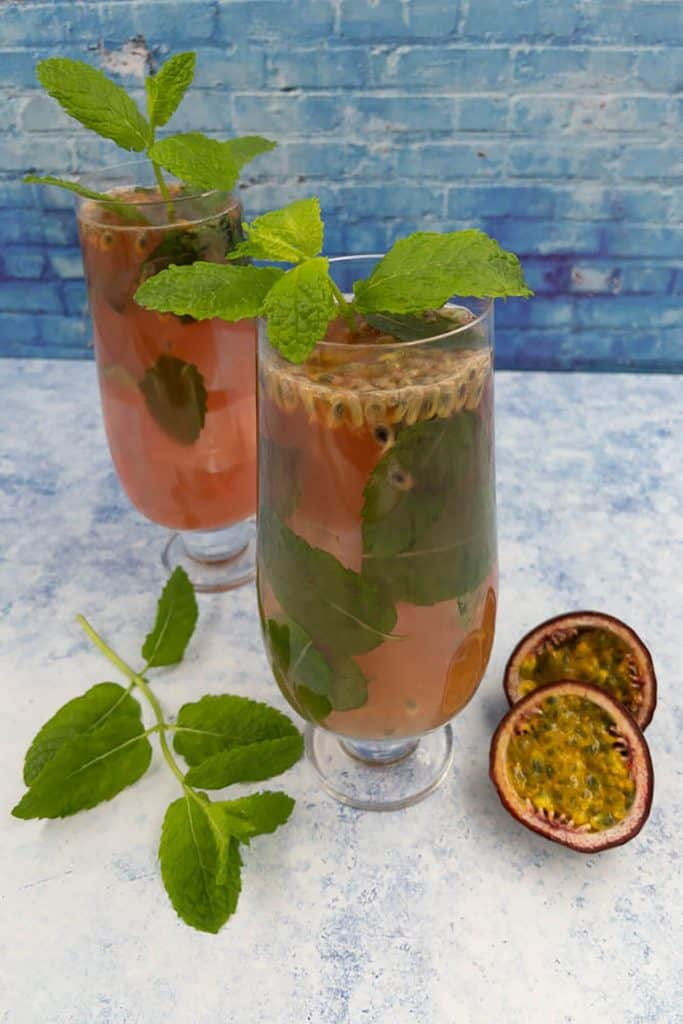 Homemade passion fruit mojitos with mint leaves garnish and passion fruit seeds