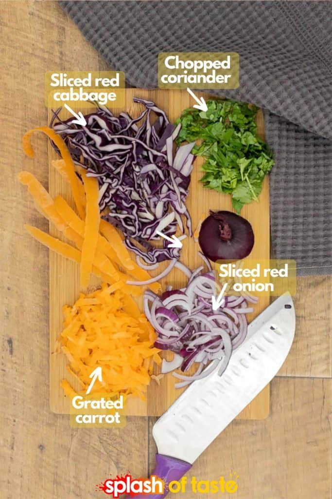 Ingredients for red cabbage slaw recipe with thinly sliced red cabbage, chopped coriander, grated carrot and thinly sliced red onion on a chopping board with a sharp knife