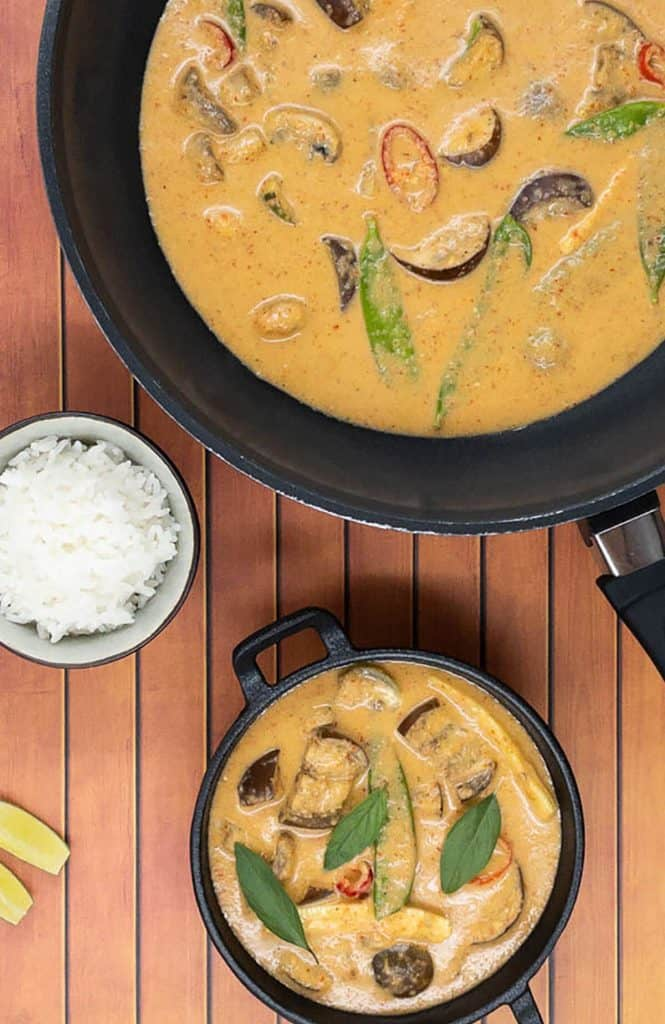 Vegan Thai red curry in a pan, a cast iron dish and with jasmine rice