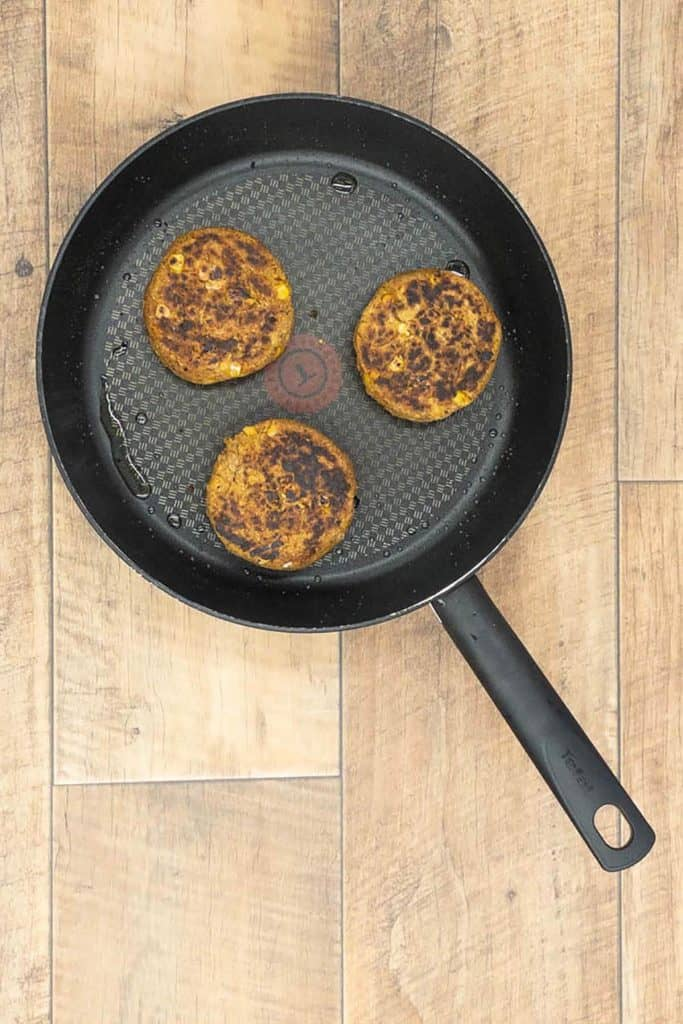 Three chickpea patties fried in a pan