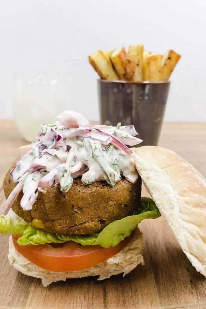 Vegan chickpea burger with chips and a glass of cold lemonade