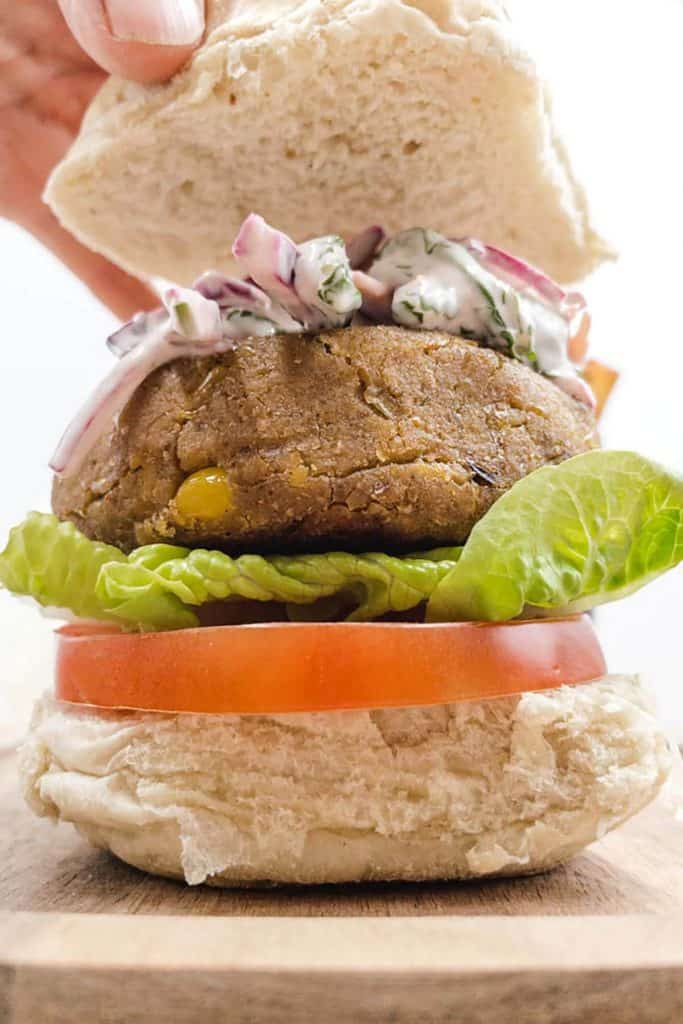 Placing the lid on a veggie burger with chickpeas, lettuce, tomato and a bun