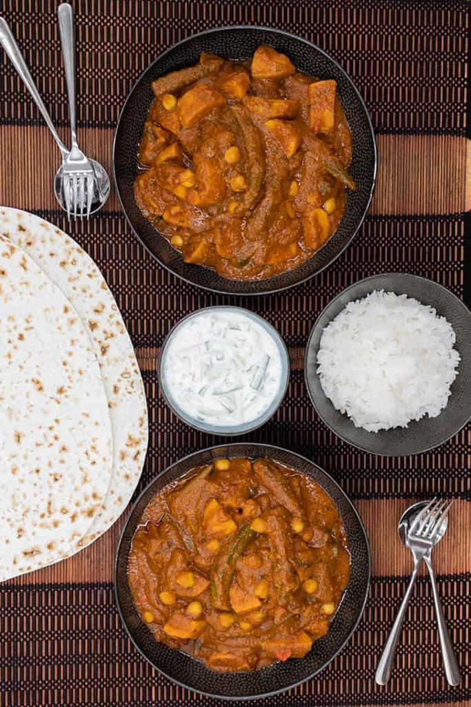 Dinner is served, vegetarian vindaloo in dishes, with vegetables and chickpeas, served with basmati rice, mint raita and chapati