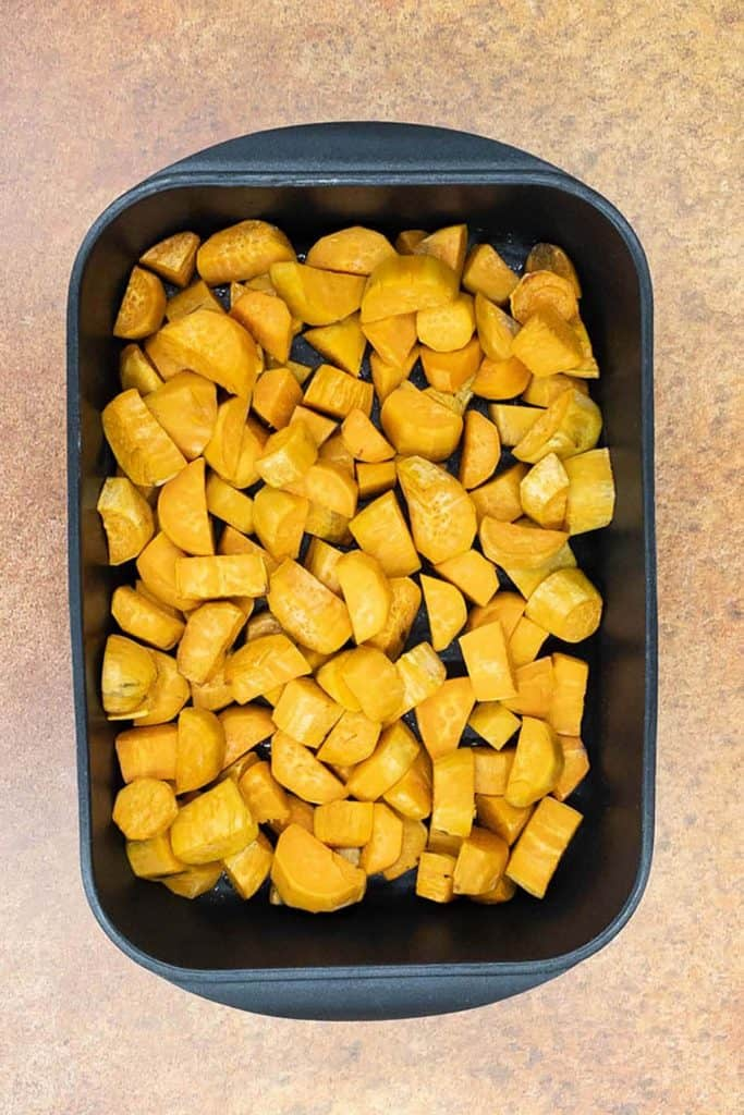 A roasting tin of sweet potatoes straight from the oven.