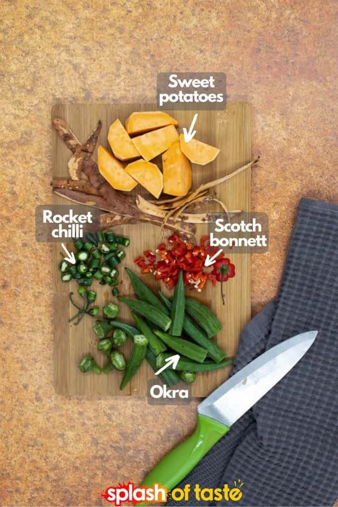 Vegetables chopped up on a chopping board, sweet potato, rocket chilli, scotch bonnet and okra, with a knife and tea towel by the board