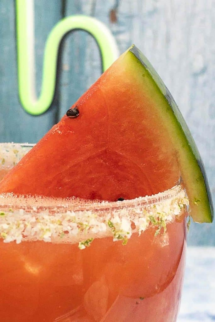 Close up of watermelon slice in a fresh watermelon margarita cocktail made with tequila