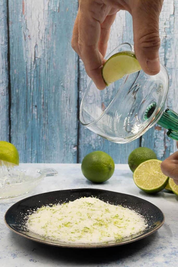 Wiping rim of cactus margarita glass with fresh lime.
