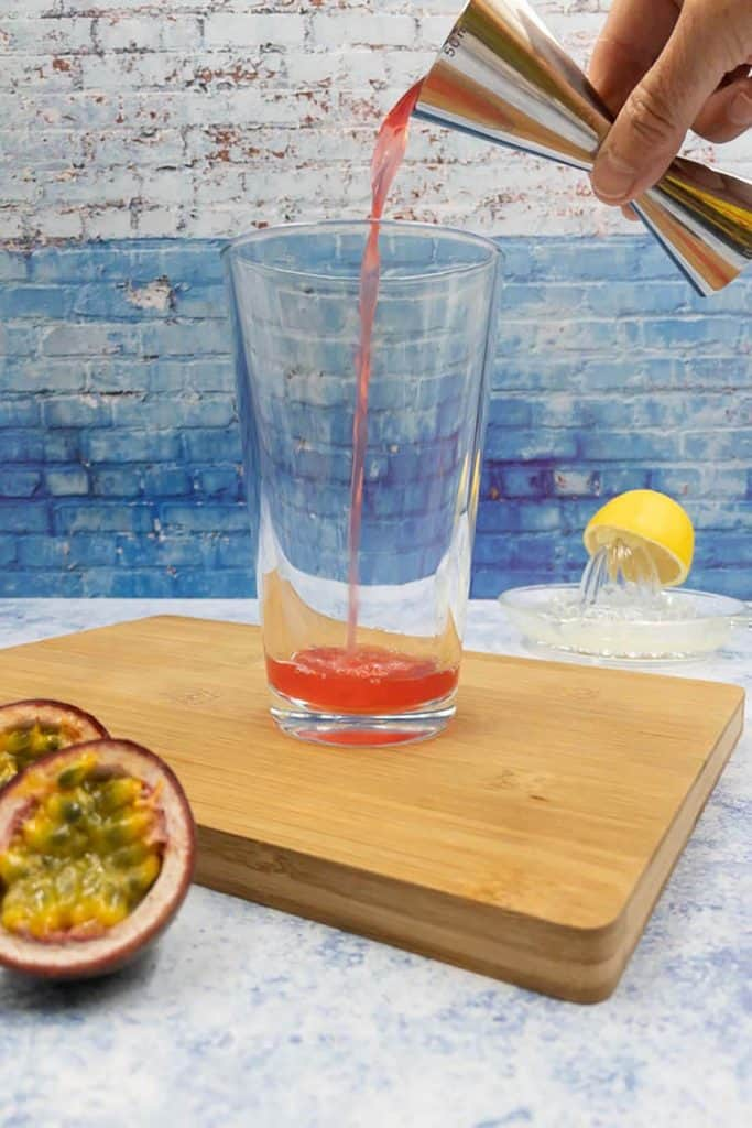 Adding passoa liqueur to a cocktail shaker.