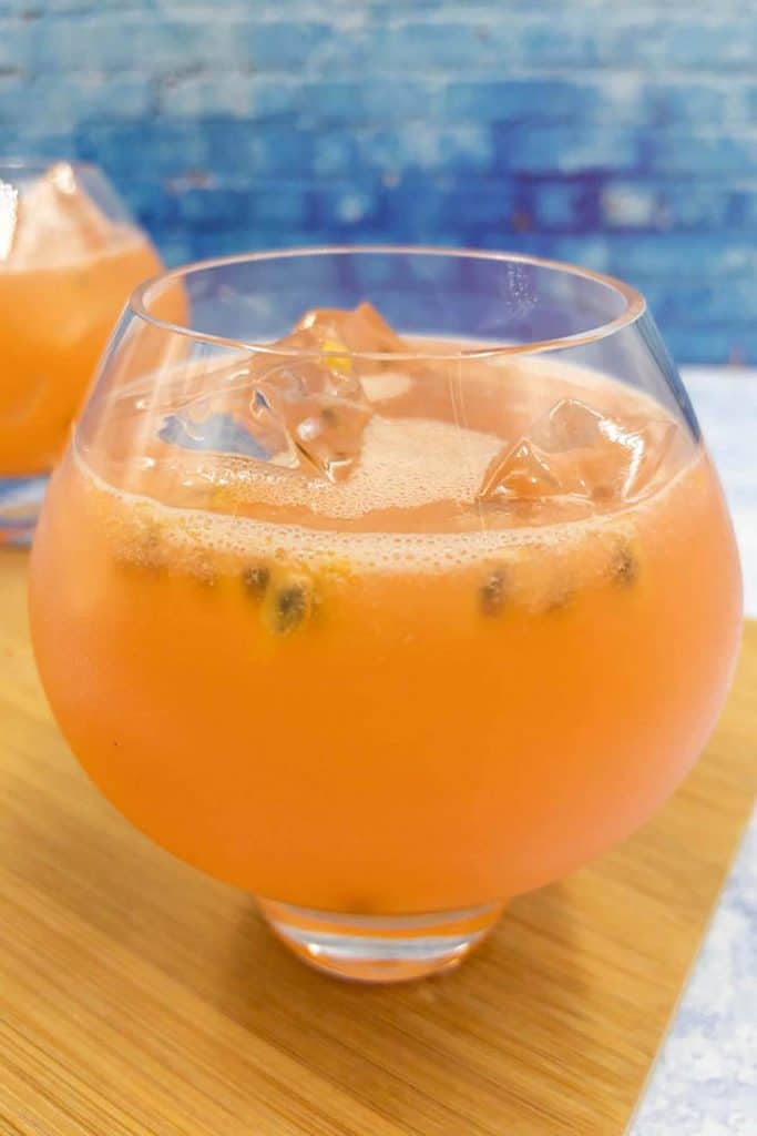An orange coloured passion fruit bramble drink with ice cubes