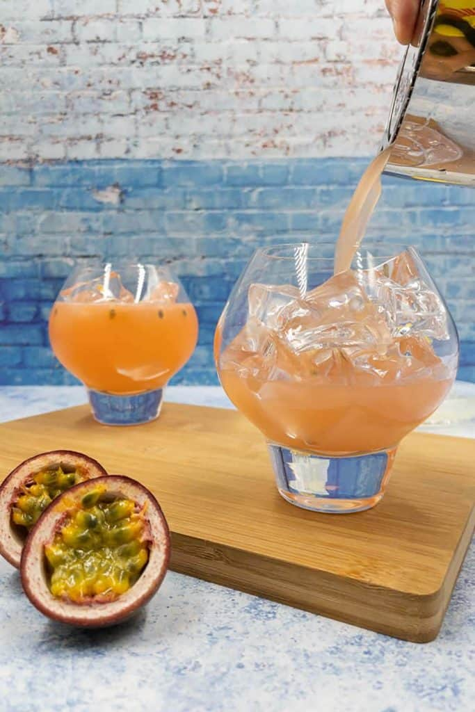 Passion fruit bramble being poured into a glass over ice