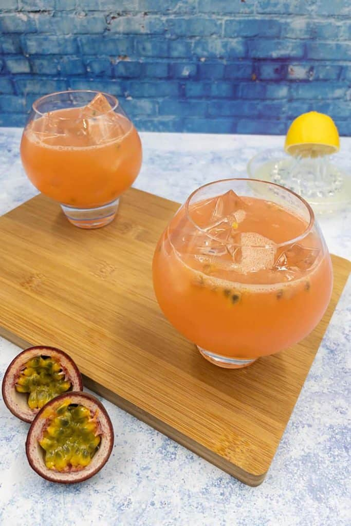 Two passion fruit cocktails with ice cubes, passion fruit and lemon juice