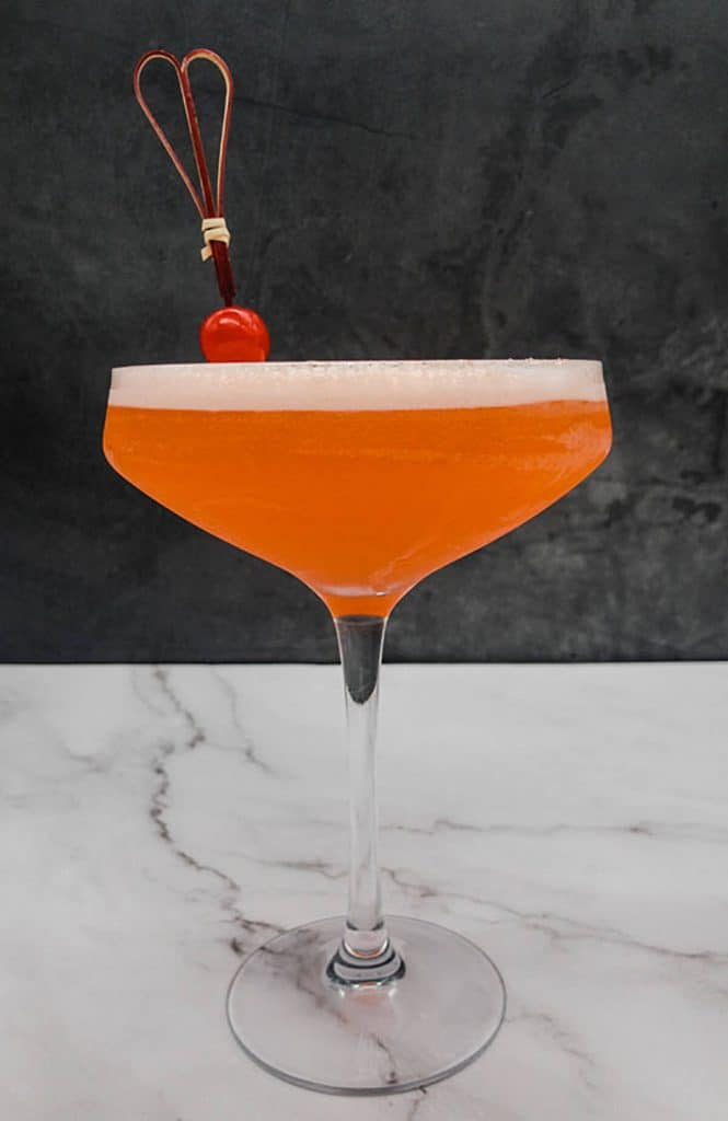 Aperol sour cocktail in a coupe cocktail glass with a maraschino cherry garnish.