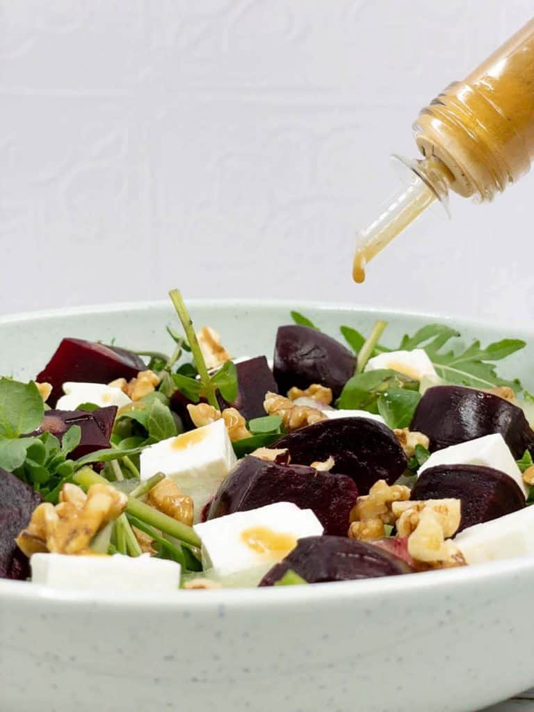 Pouring delicious balsamic dressing over a mouthwatering DIY beetroot and feta salad made from roasted beets, rocket, watercress, chopped walnuts and cubed feta cheese.