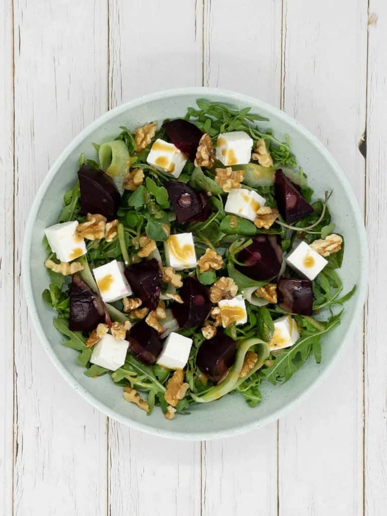 A bowl of beetroot and feta salad with rocket, watercress, roasted beets, chopped feta, chopped walnuts sprinkled on and balsamic dressing drizzled over
