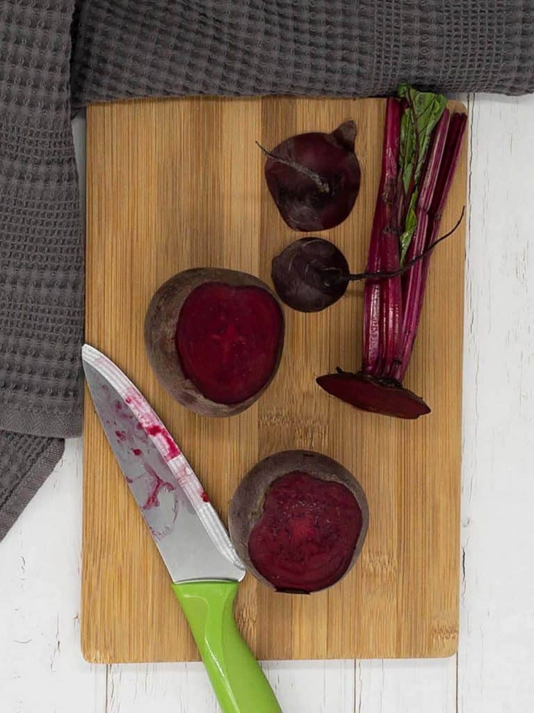 Raw beets on a chopping board having been top and tailed