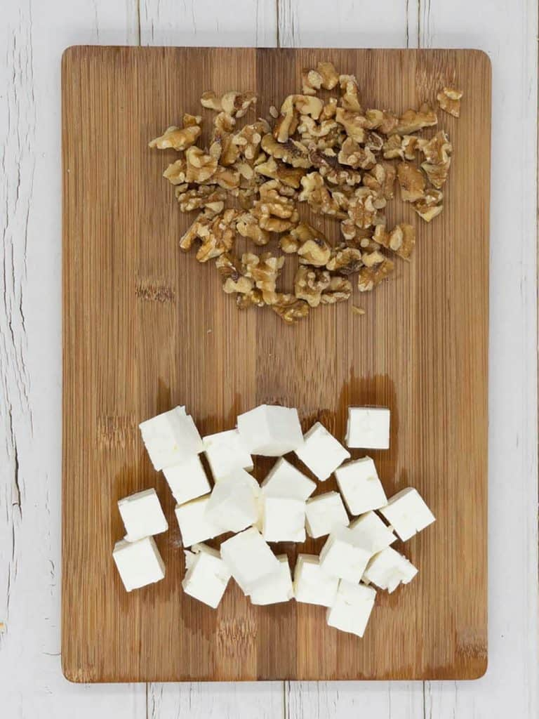 Cubed feta cheese and chopped walnuts on a chopping board ready to go into a homemade beetroot and feta salad