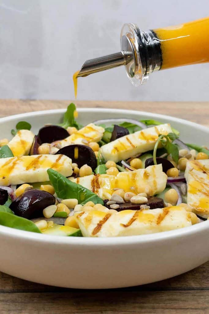 Tangy chili and lime salad dressing being drizzled over a healthy halloumi salad.