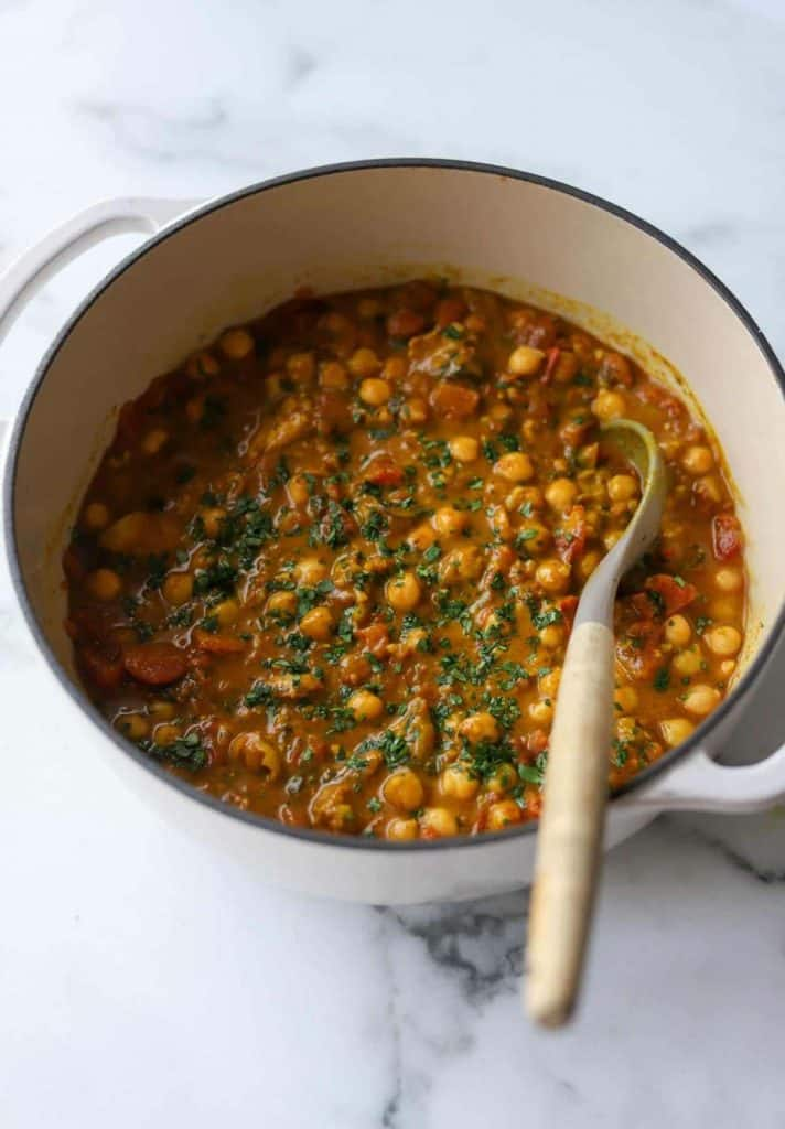 A pot of chickpea coconut curry with a wooden spoon in it.