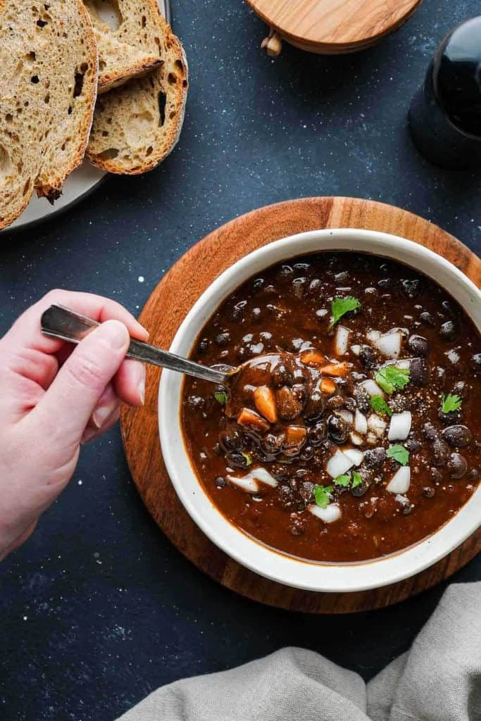 Black bean soup in a bowl with black beans showing in a sauce.