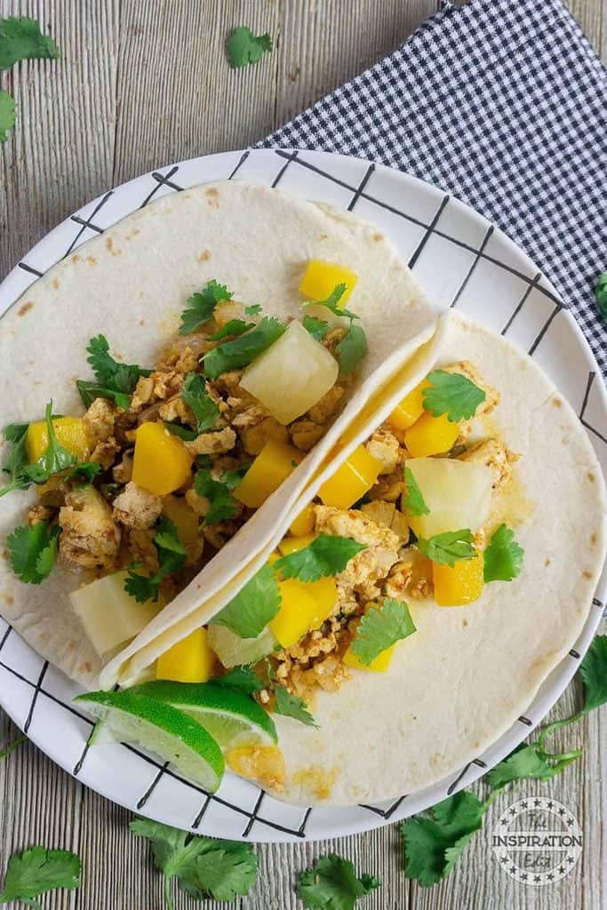 Delicious tropical vegan tacos with lime wedges and cilantro.