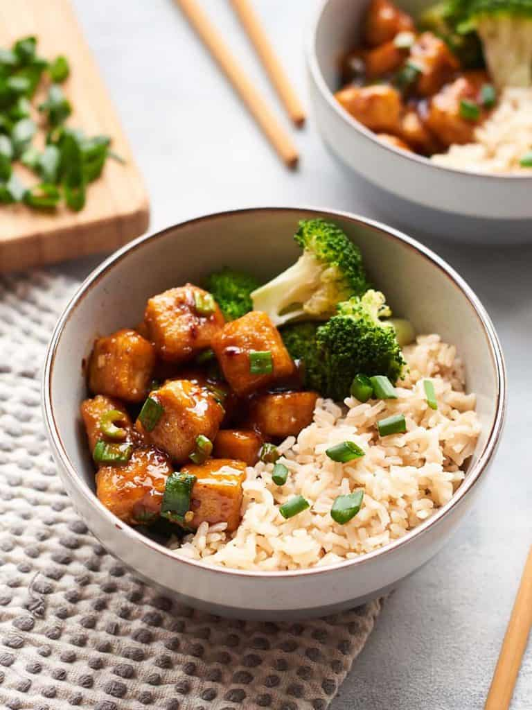 Delicious vegan mongolian beef made out of tofu or seitan with broccoli, scallions and rice.