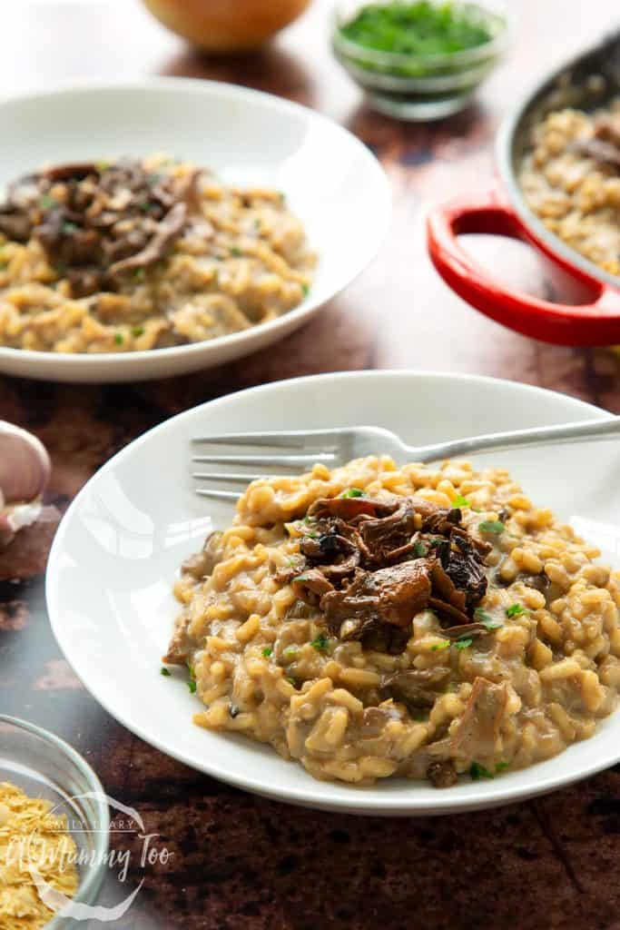 Bowls of mushroom risotto just cooked and ready to eat with shitake mushrooms on top.