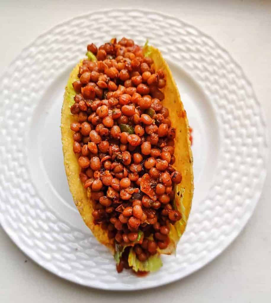 Delicious lentil taco meat in a taco on a plate.