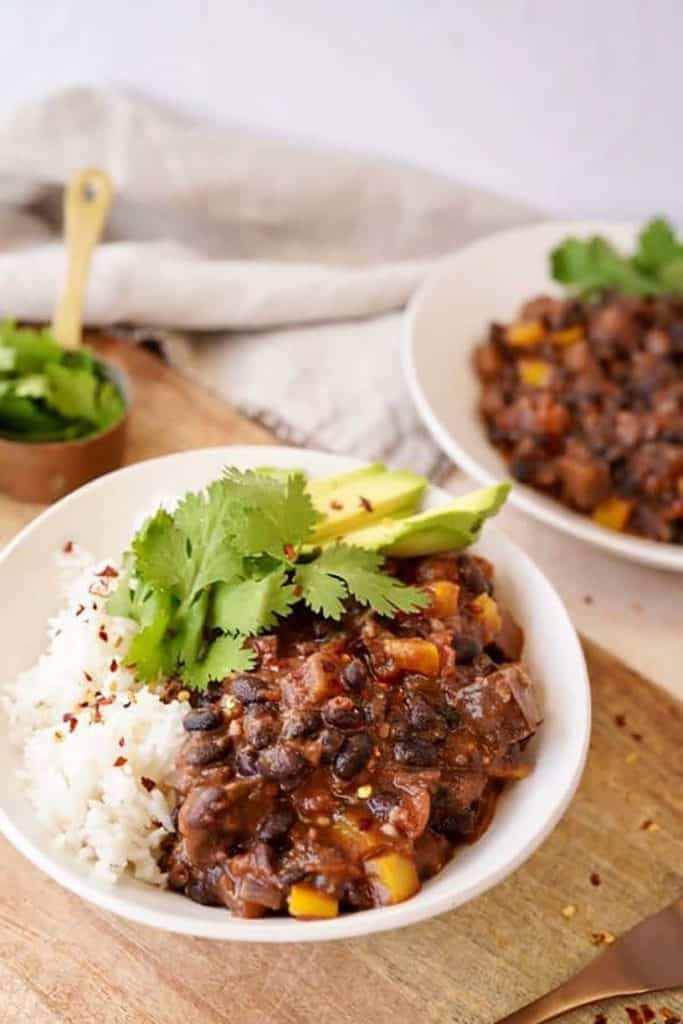 Two bowls of black bean chili with lots of black beans and rice.