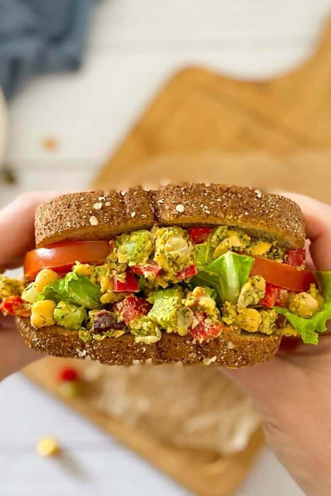 Large chickpea and salad sandwich full of veggies, with tomatoes and lettuce.