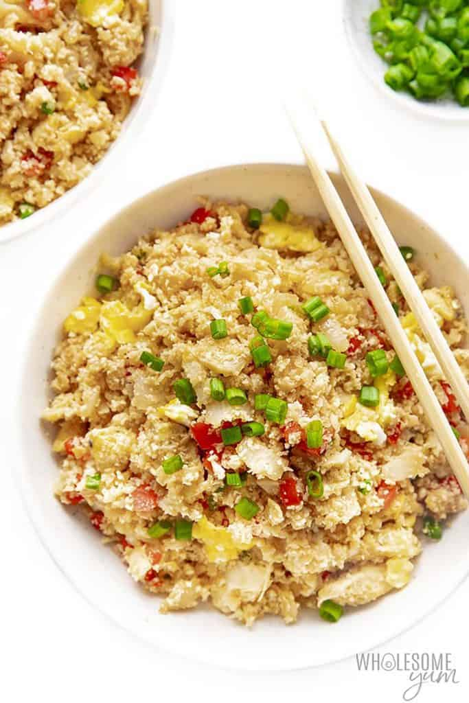 A bowl of keto cauliflower rice with chop stick, scallions scattered on top.