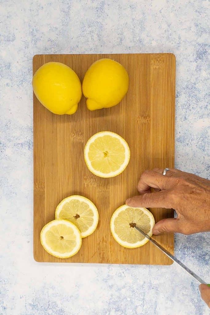 Slicing a lemon garnish for lemon margaritas