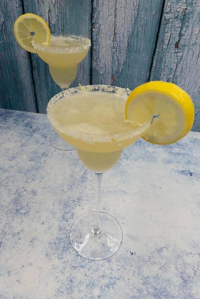 Two homemade lemon margaritas with lemon wheel garnish