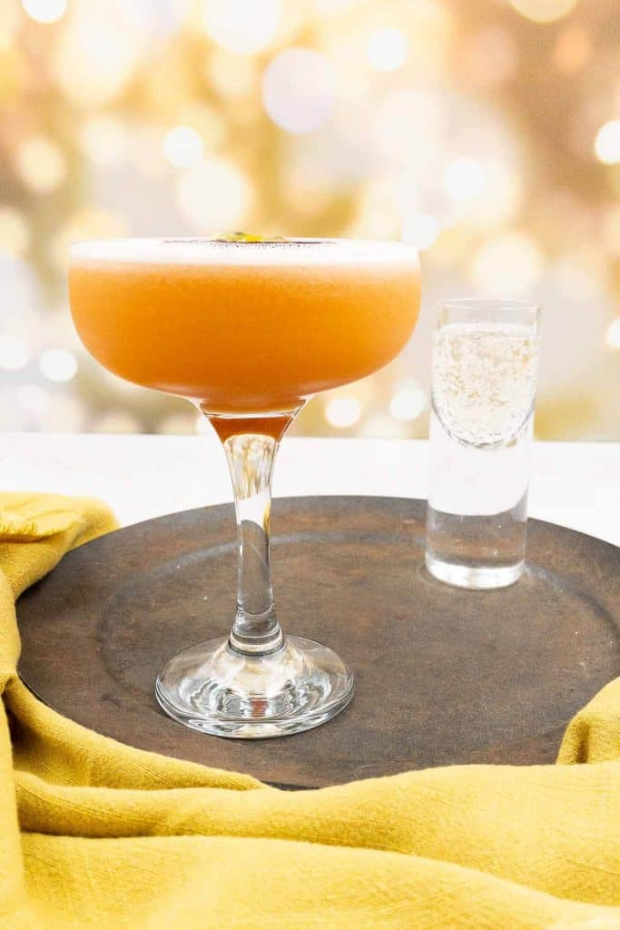 Pour passoa from a jiggle into a cocktail shaker with passion fruits in the background