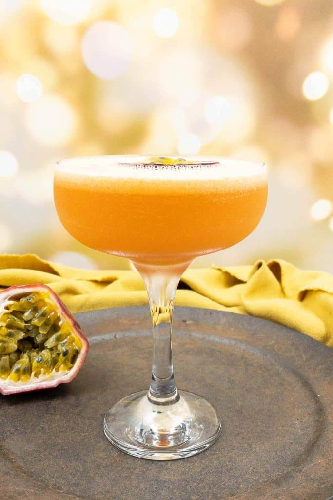 Making pornstar martini drinks pour passion fruit juice into a cocktail shaker
