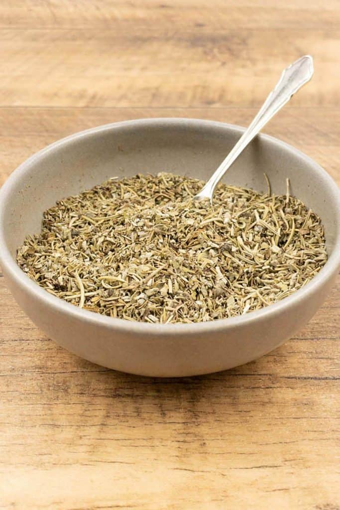 A bowl of savory homemade seasoning with a spoon ready to use.