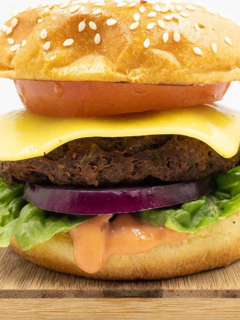 Fresh vegan burger, in a delicious brioche seeded bun, vegan burger sauce, fresh lettuce, red onion, a slice of vegan cheese and a tomato.