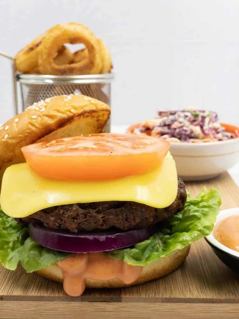 Homemade vegan seitan burger patty, with tomato, lettuce, vegan cheese, slaw, veggie burger sauce and onion rings in a basket