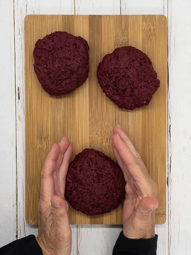 Shaping three seitan burgers on a chopping board.