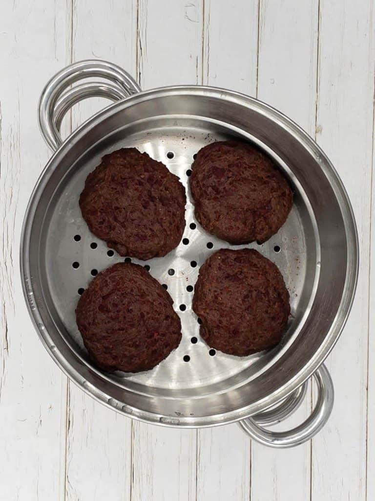 Four seitan burgers in a steamer pan.