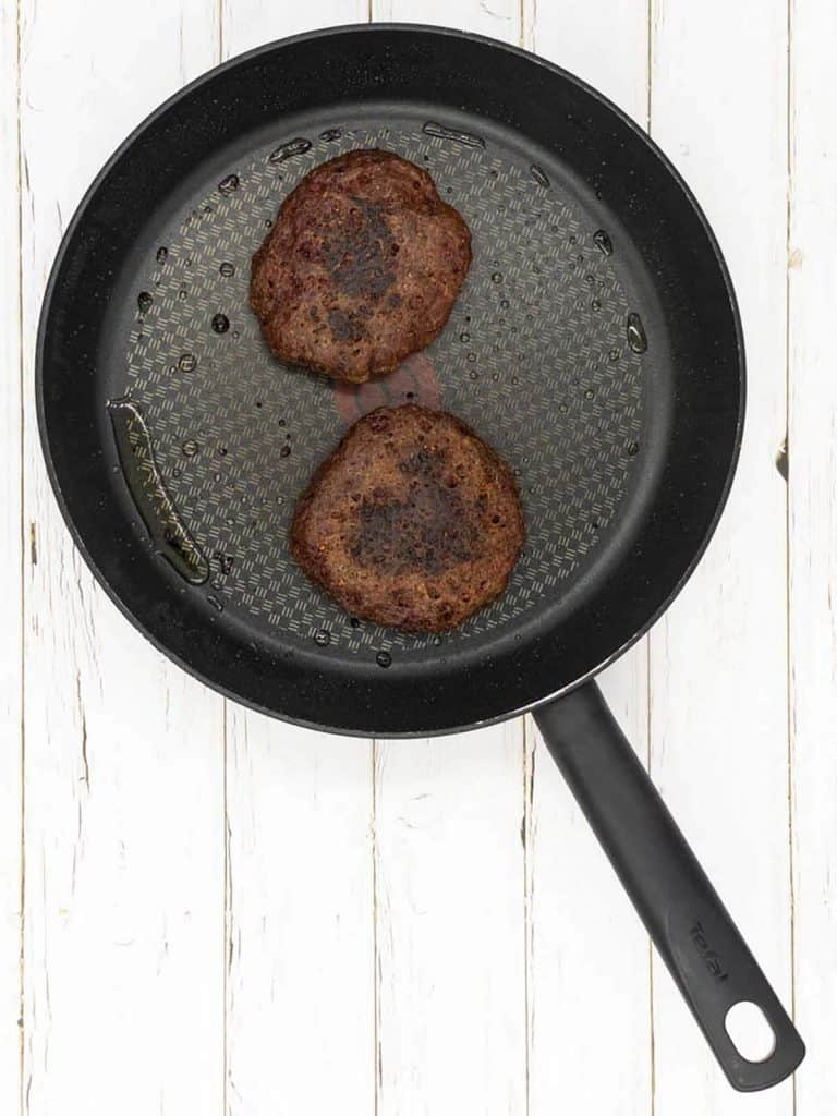 Two vegan burgers with olive oil frying in a frying pan.