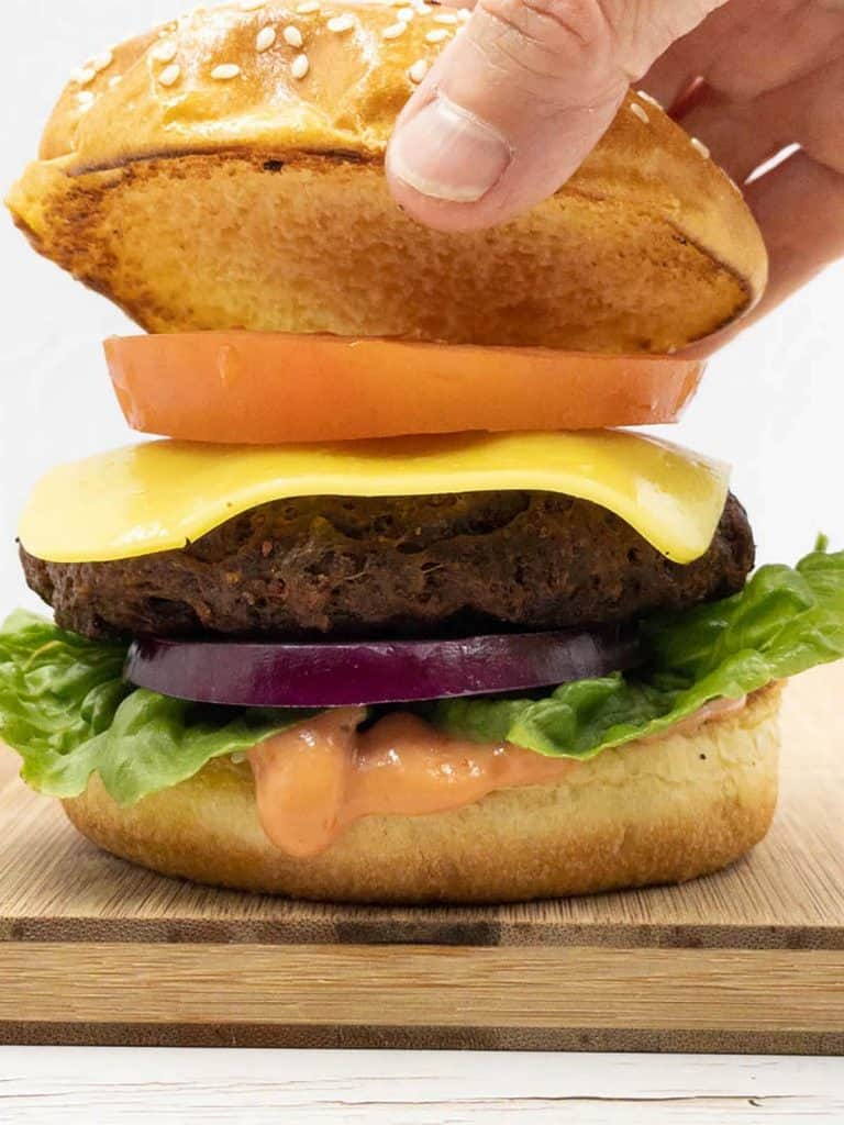 Adding the burger lid to a delicious seitan vegan burger that's full of flavor.