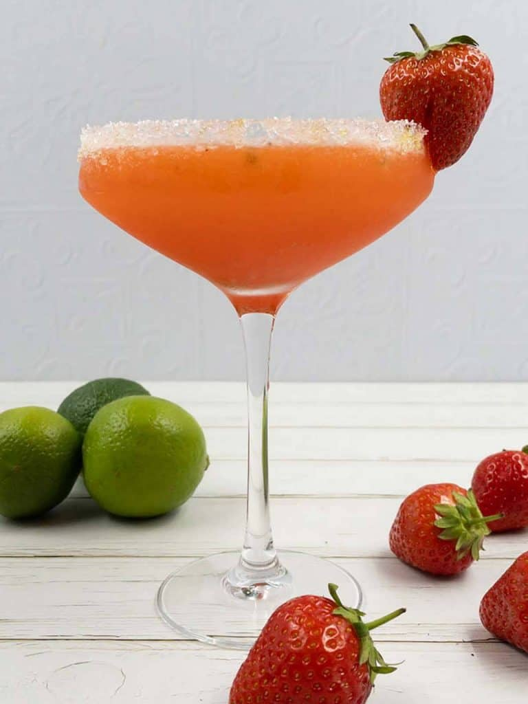 Refreshing strawberry daiquiri in a cocktail glass, with fresh strawberries and lime around it.