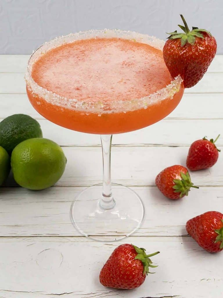 A couple glass filled with homemade strawberry daiquiri, a lime sugar rim and a strawberry garnish.