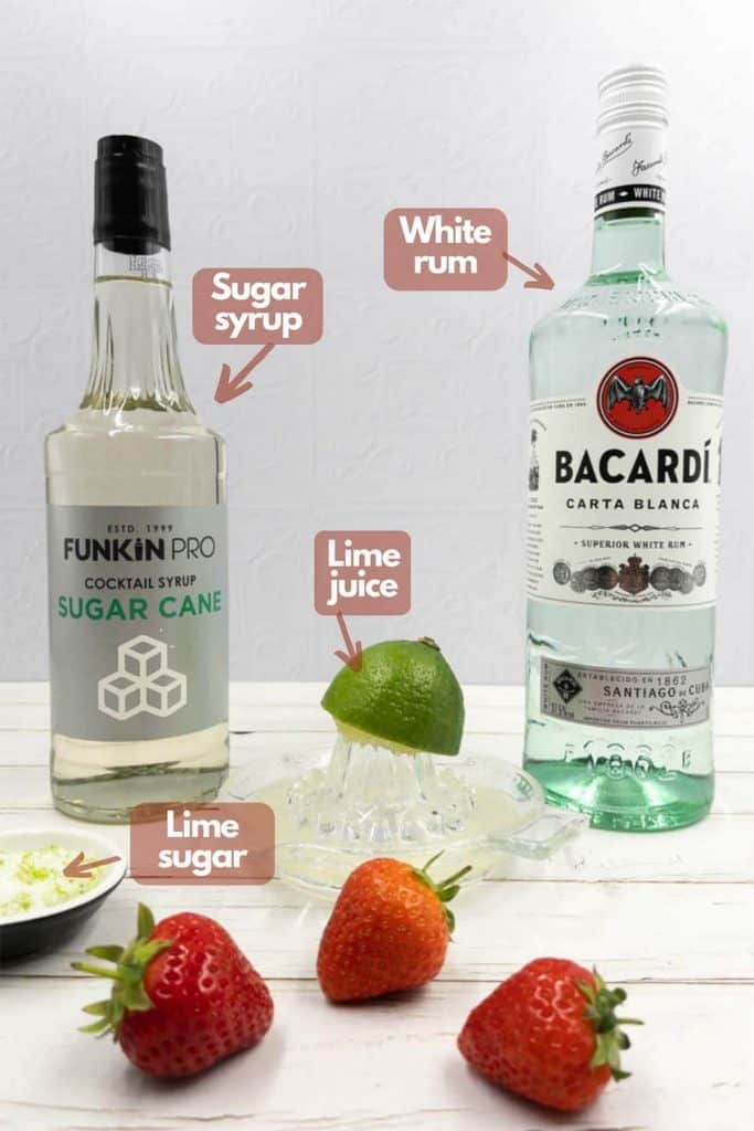 Ingredients for a strawberry daiquiri recipe, sugar syrup, white rum, lime juice and lime sugar.