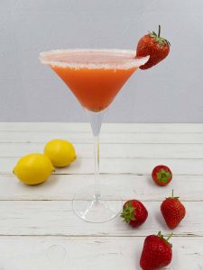 Stunning strawberry martini cocktail drink with strawberries and lemons on the floor around it.