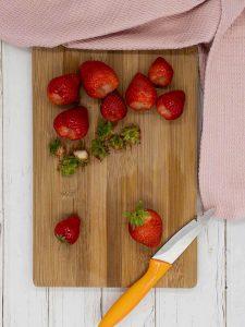 Hulling fresh strawberries on a chopping boardd.