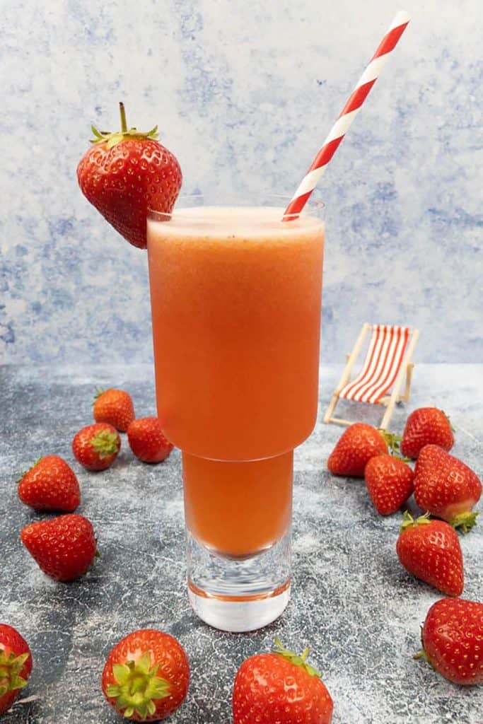 Homemade strawberry lemonade cocktail with a fresh strawberry garnish, a straw and a deckchair.