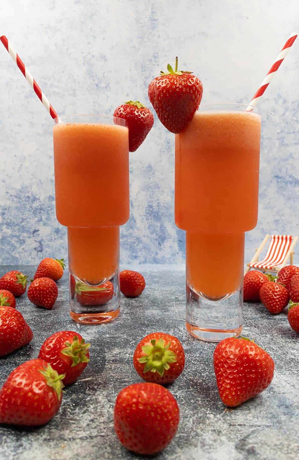 Two strawberry lemonade vodka cocktails with fresh strawberries, striped straws and a deck chair.
