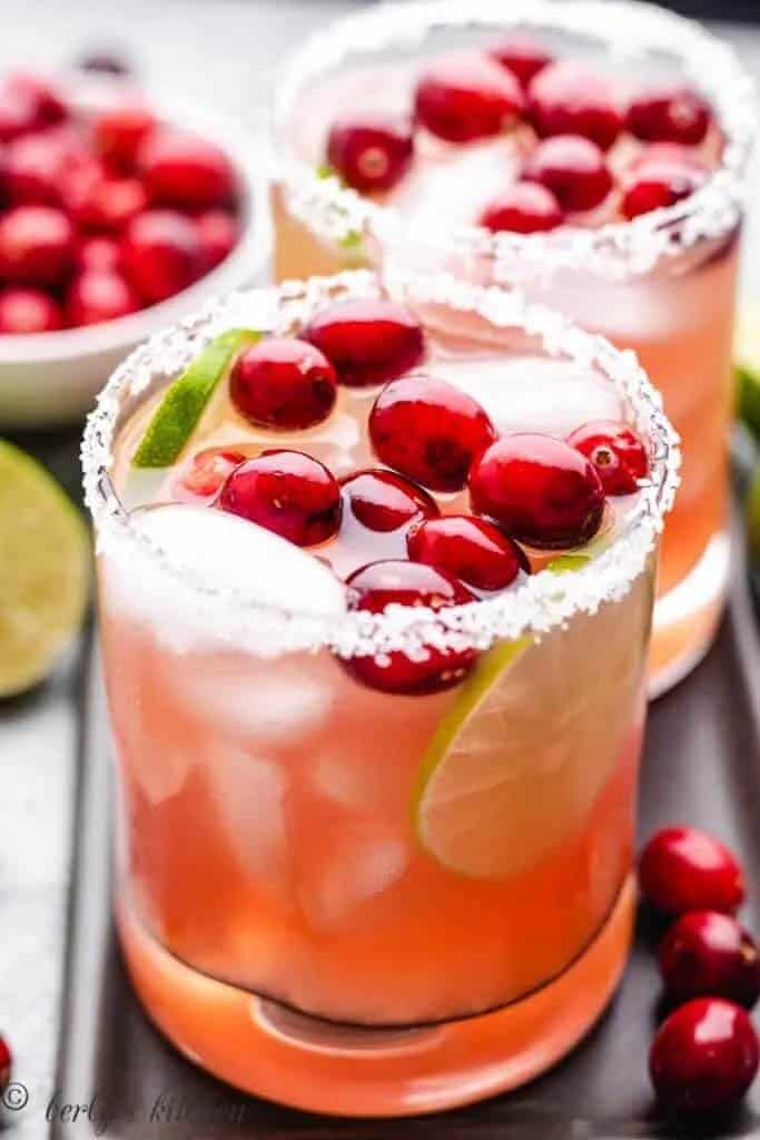 Beautiful cranberry margaritas in cocktail glasses with fresh cranberry as garnish
