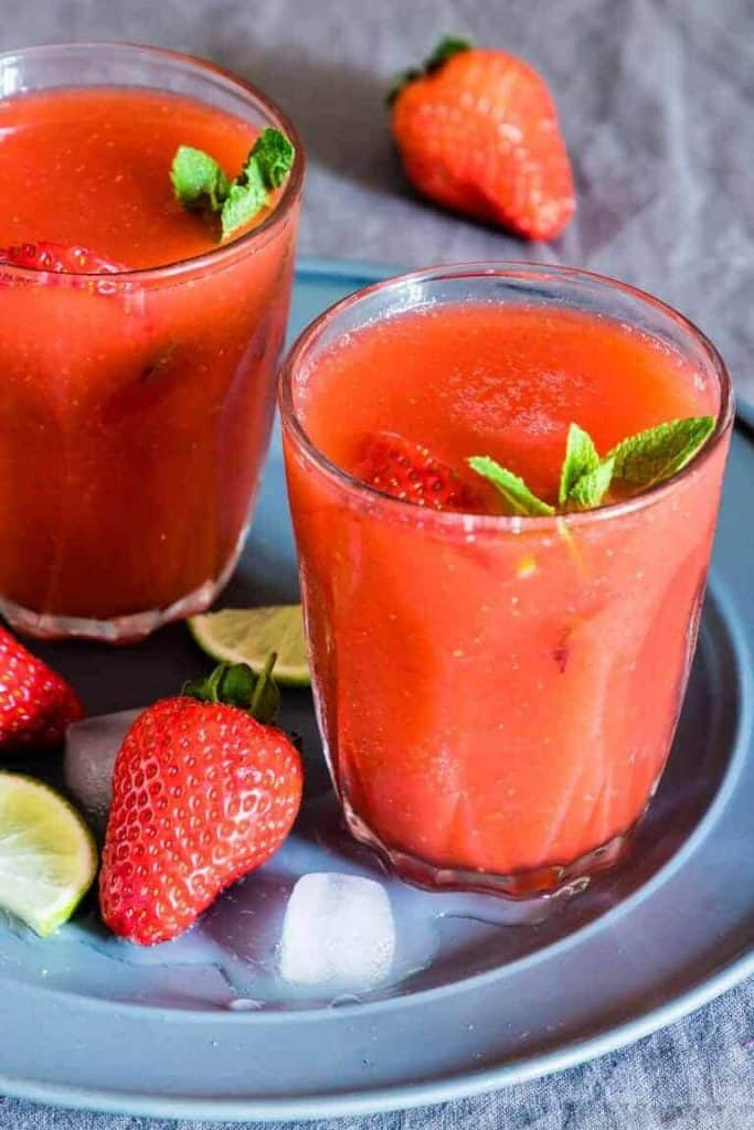 Frozen strawberry margarita in a chilled glass with a fresh strawberry garnish, lime wedges and ice cubes